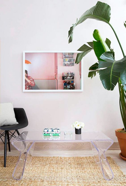 lucite coffee table with green banana leaf plant and pink framed photograph / sfgirlbybay