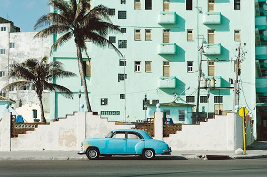 mint building exterior and vintage blue car in cuba. / sfgirlbybay