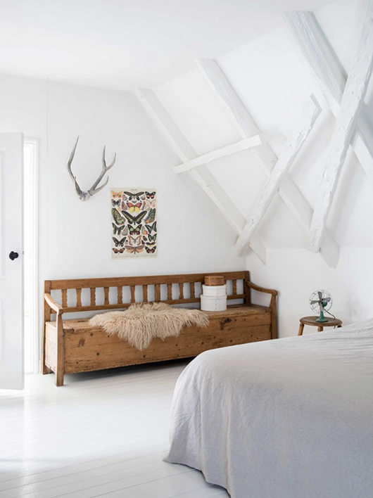 white bedroom with beamed ceilings and painted floors and wood bench / sfgirlbybay