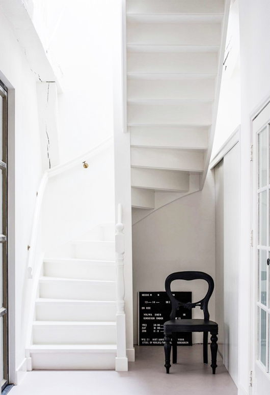barn house white hallway with black chair and message board / sfgirlbybay