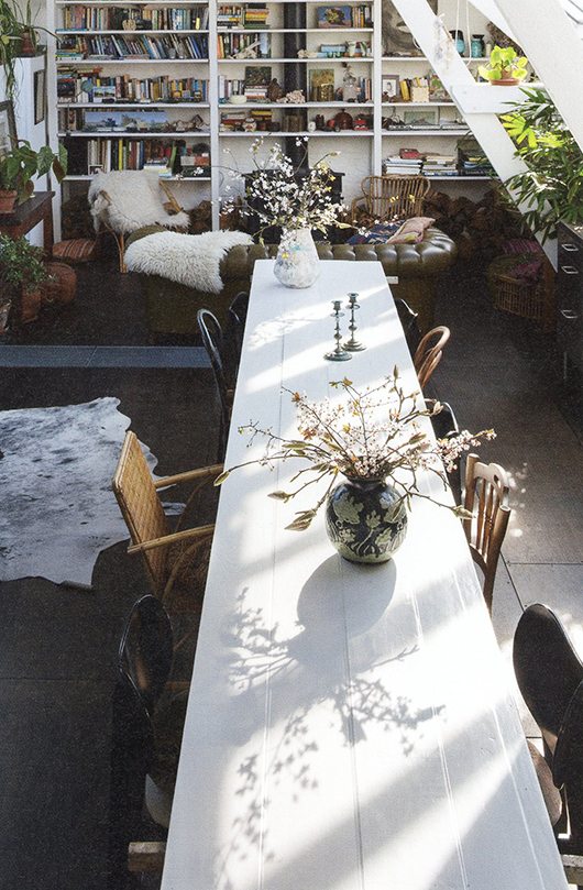 long white table in bohemian modern living room with built-in bookshelves and potted houseplants / sfgirlbybay