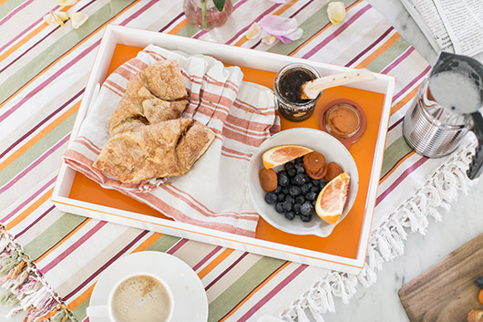 orange and white tray with breakfast foods, nespresso coffee and Aeroccino4 milk frother on striped kitchen linens / sfgirlbybay