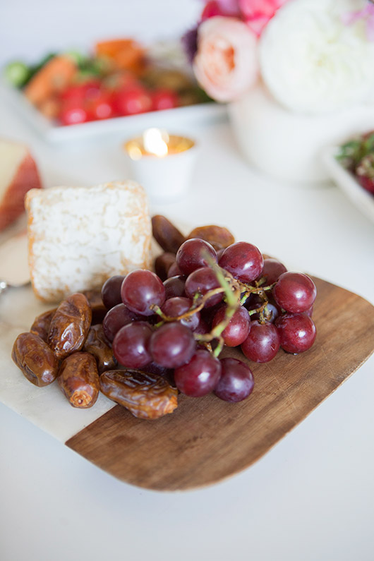 wood cutting board with cheese and grapes and dates / sfgirlbybay