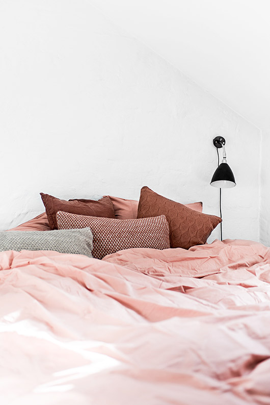 pink bedding with black light fixture on white wall / sfgirlbybay
