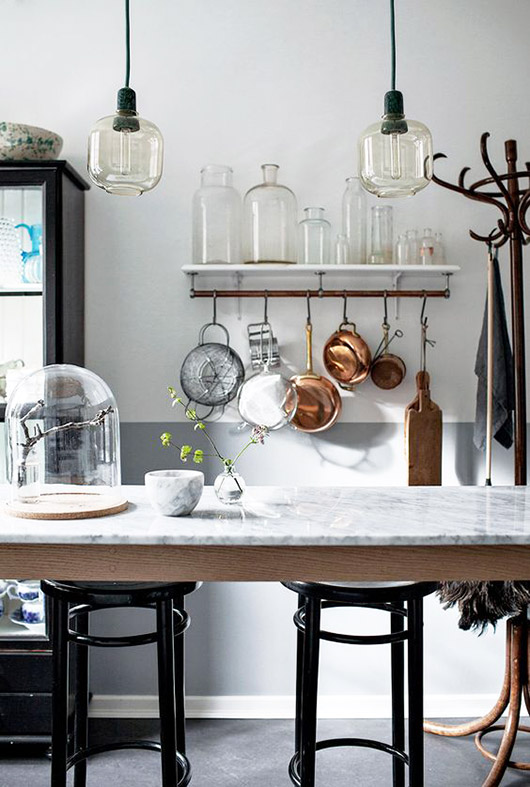 two glass pendant lamps hung above marble table with glass jars and kitchen tools hung on the wall behind the table / sfgirlbybay