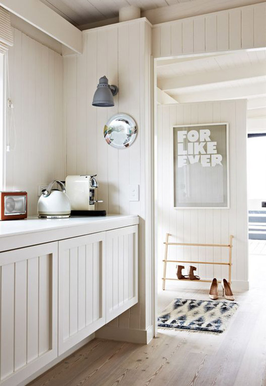 modern white kitchen with whitewashed wood floors and poster that reads