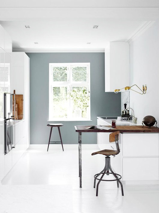 white minimalist kitchen with gray accent wall and wood and metal bar and stools / sfgirlbybay