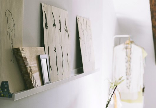 floating white shelf with art leaned and layered along it / sfgirlbybay