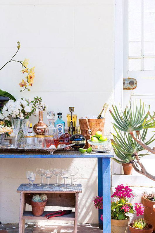 colorful home bar in front of a white wall with potted plants / sfgirlbybay