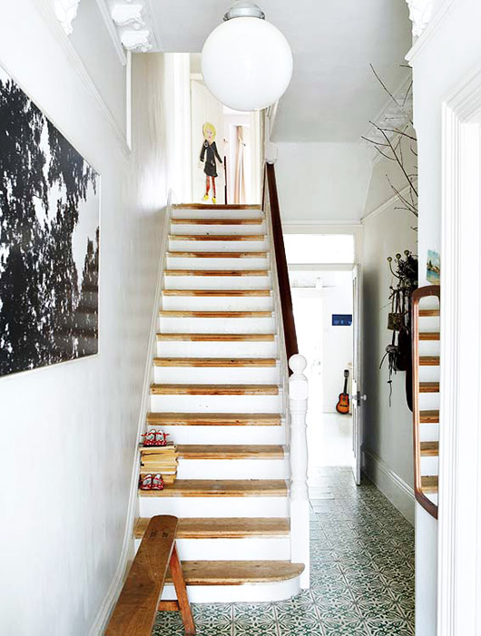 white staircase with globe light fixture and black and white art on wall / sfgirlbybay
