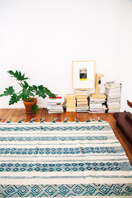 books piled in corner of modern room with moroccan area rug / sfgirlbybay