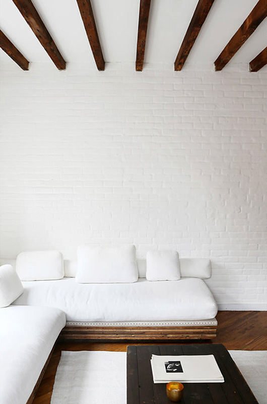white sofa with white brick walls and wood beamed ceiling / sfgirlbybay