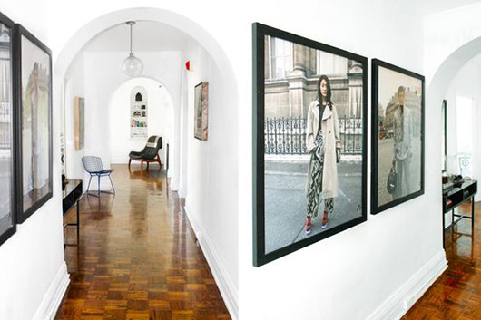 arched hallway with oversized framed photographs on the walls. / sfgirlbybay
