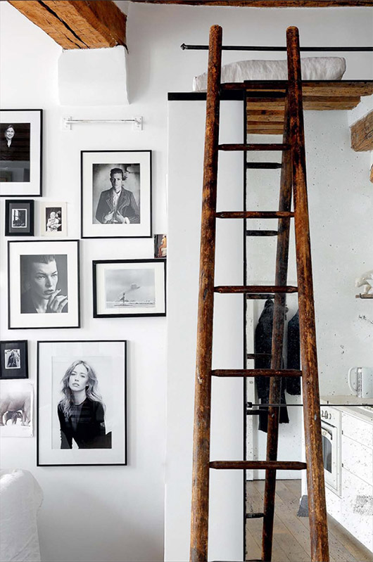 black and white photo wall with wooden ladder. / sfgirlbybay