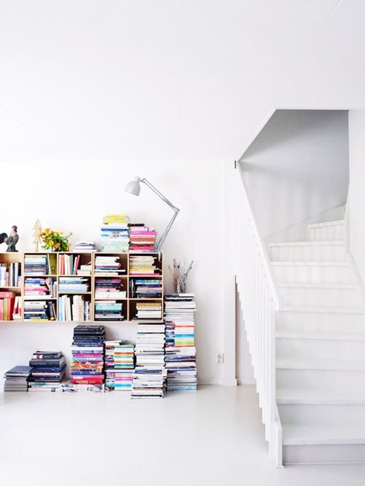 books piled below bookcase in white room. / sfgirlbybay