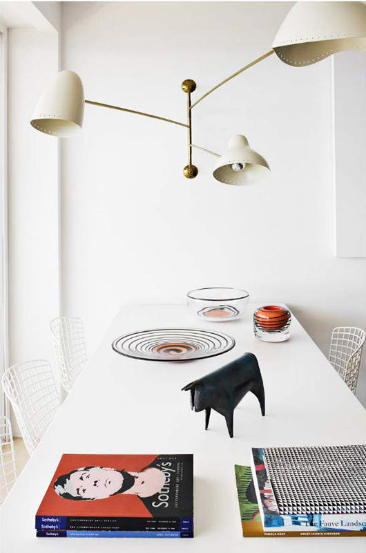 white dining table and lamps with colorful books. / sfgirlbybay