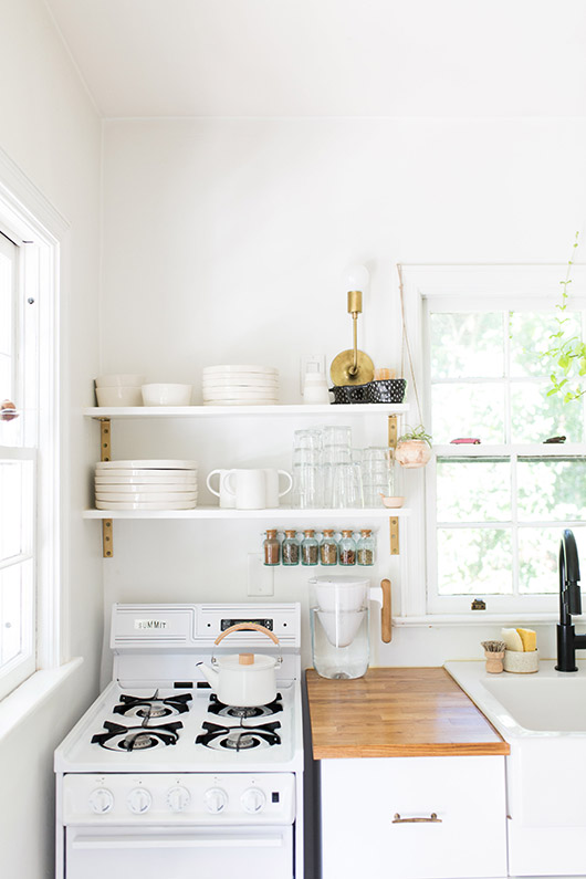 open kitchen shelving above stove and cutting board. / sfgirlbybay