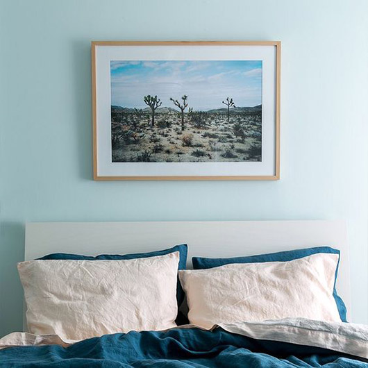 desert photograph above bed with blue bedding. / sfgirlbybay