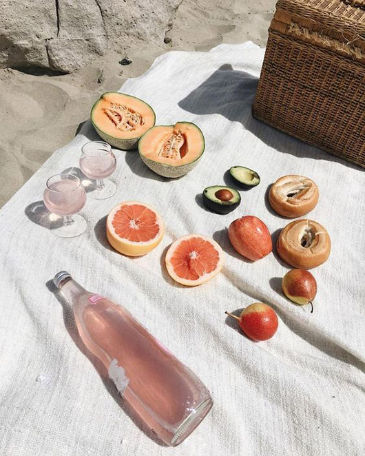 simple picnic arranged on white blanket on the beach. / sfgirlbybay