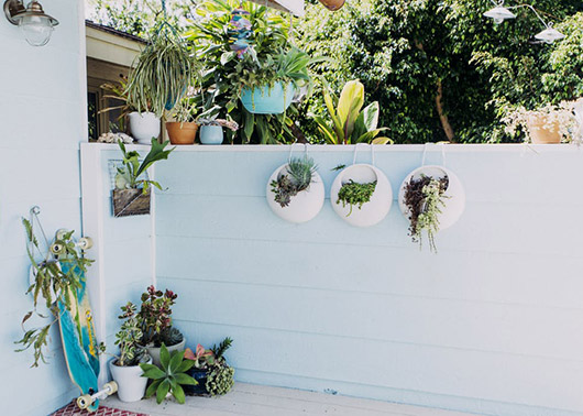 hanging succulent planters on white patio wall. / sfgirlbybay