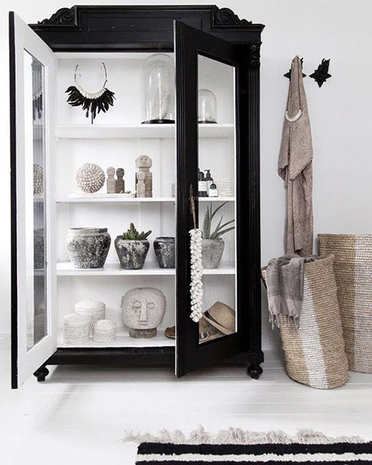 large black cabinet with glass doors and curated collection of decor inside. / sfgirlbybay