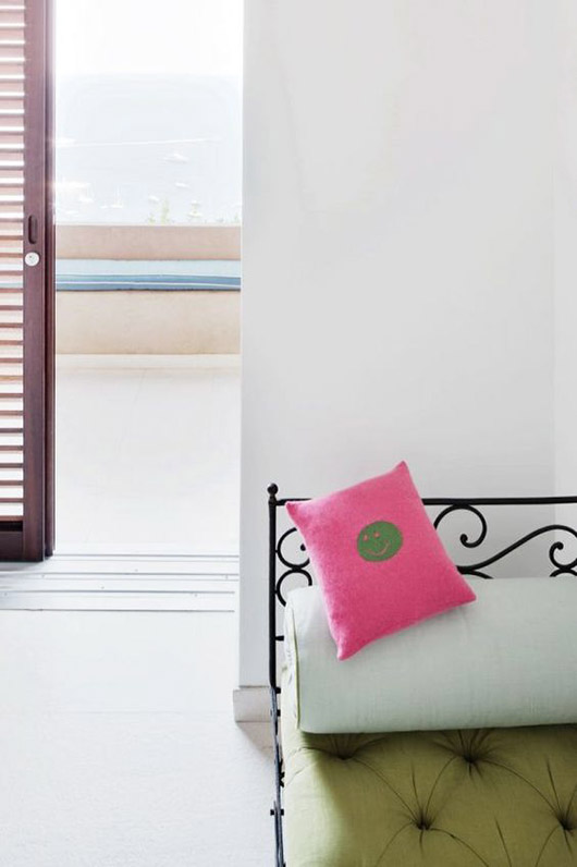 pink smiley face throw pillow on wrought-iron daybed. / sfgirlbybay