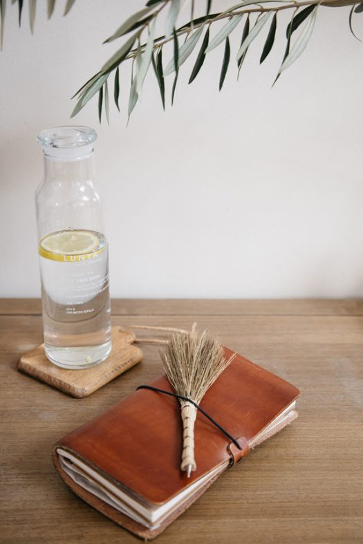 leather journal and pen with water carafe. / sfgirlbybay
