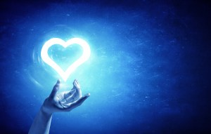 Person holding digital glowing heart in palm