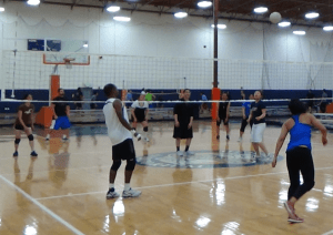 Men and women playing volleyball indoors.