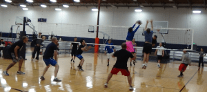 Indoor volleyball players blocking an attack.