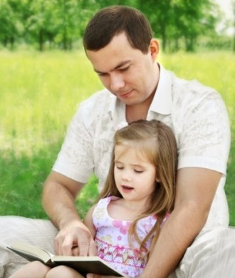 Father with daughter reading in the park