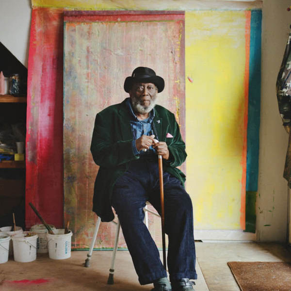 Photograph of Frank Bowling in front of one of his abstract paintings