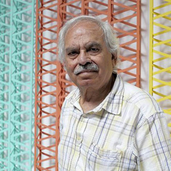 Image of Rasheed Araeen in front of one of his geometric sculptures