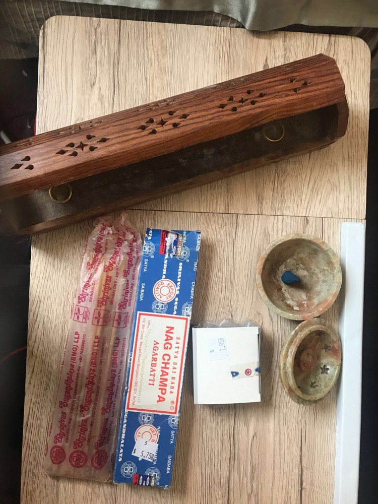 a soapstone incense burner with a cone incense inside, a pack of incense sticks, and a long wooden incense burner rest on a table. A small box is on the table next to a larger one both are labeled Nag Champa.