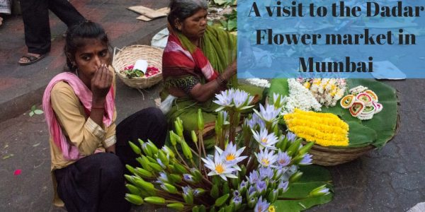 dadar flower market - mumbai-maharashntra- india- journey- trip- ttot- lillies in a basket- two women selling flowers in a basket by the roadside