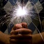 Man's hands holding a lit sparkler