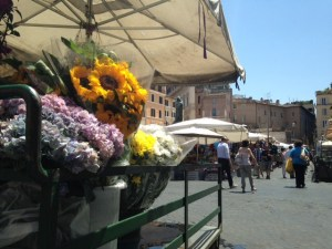 A statue of Bruno can be seen peeking beyond the sunflowers in the market.