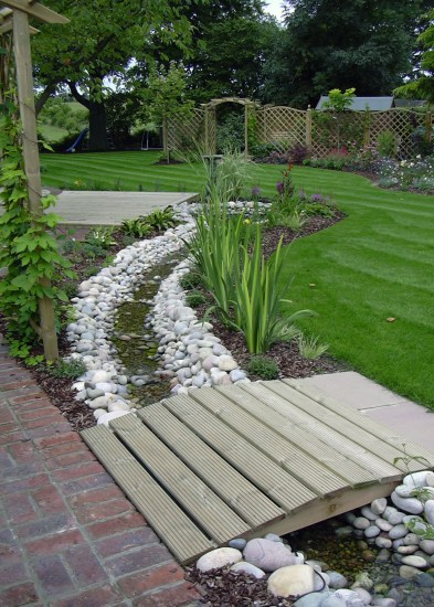Gentle bridge leads to the lawn over the meandering water rill in this medium sized garden.