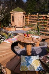 Wood and slate RHS Flower Show Cardiff 2015 garden with round table and wooden childrens den