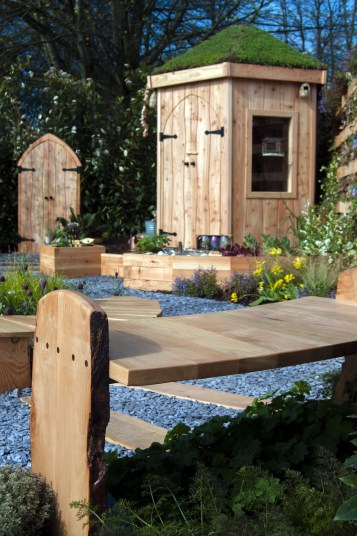 Garden Design - Wooden bench leading the eye to a hexagonal childrens den at the RHS Flower Show Cardiff 2015