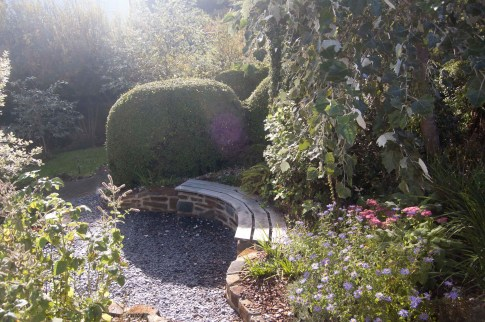 A garden design showing a blue stone walling with an oak bench top give a private area to sit and enjoy the garden in this coastal garden.