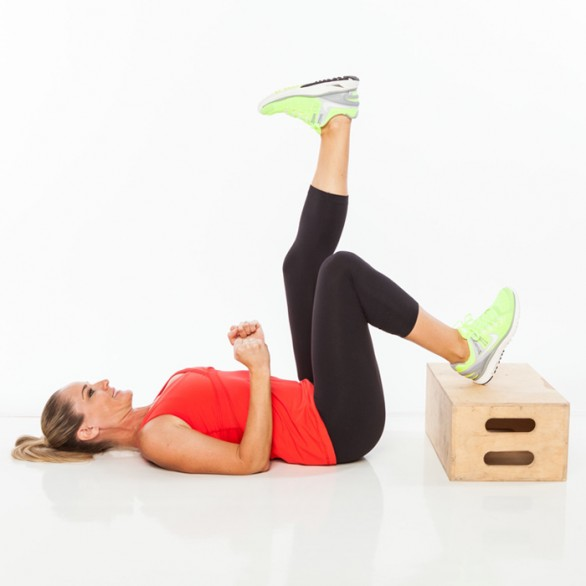 Lie faceup with elbows bent 90-degrees by sides, feet flexed, and heels on top of step (bring hips close enough to step that knees line up over hips). Extend left leg as straight as possible to ceiling.