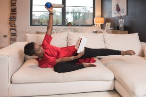 Reading on the sofa whilst doing Pilates exercises