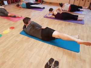 Man and women laying on Pilates mats stretching legs in Pilates exercise movement