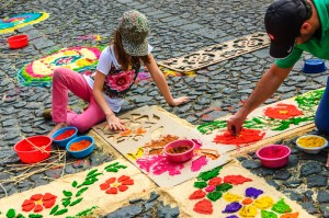 Antigua, Guatemala - March 22, 2015: Local father & daughter decorate cross shaped carpet with floral pattern of dyed sawdust using cardboard stencils for Lent procession to walk over on cobblestone street in colonial town with most famous Holy Week celebrations in Latin America.