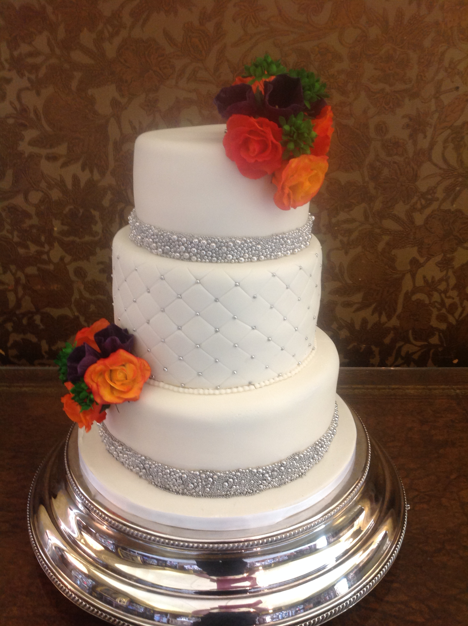 A 3 tiered stacked white cake with a posy on the top right of cherry brandy roses, Lithuansus and berries with matching posy on bottom tier. Bottom and Top tier has a band of silver balls at the base with a quilted pattern on the middle tier with silver balls