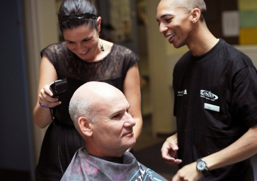 UCT Gizelle Willows gets a lesson from Jisreel Aries of CANSA before she tackles the hair of Mark Graham