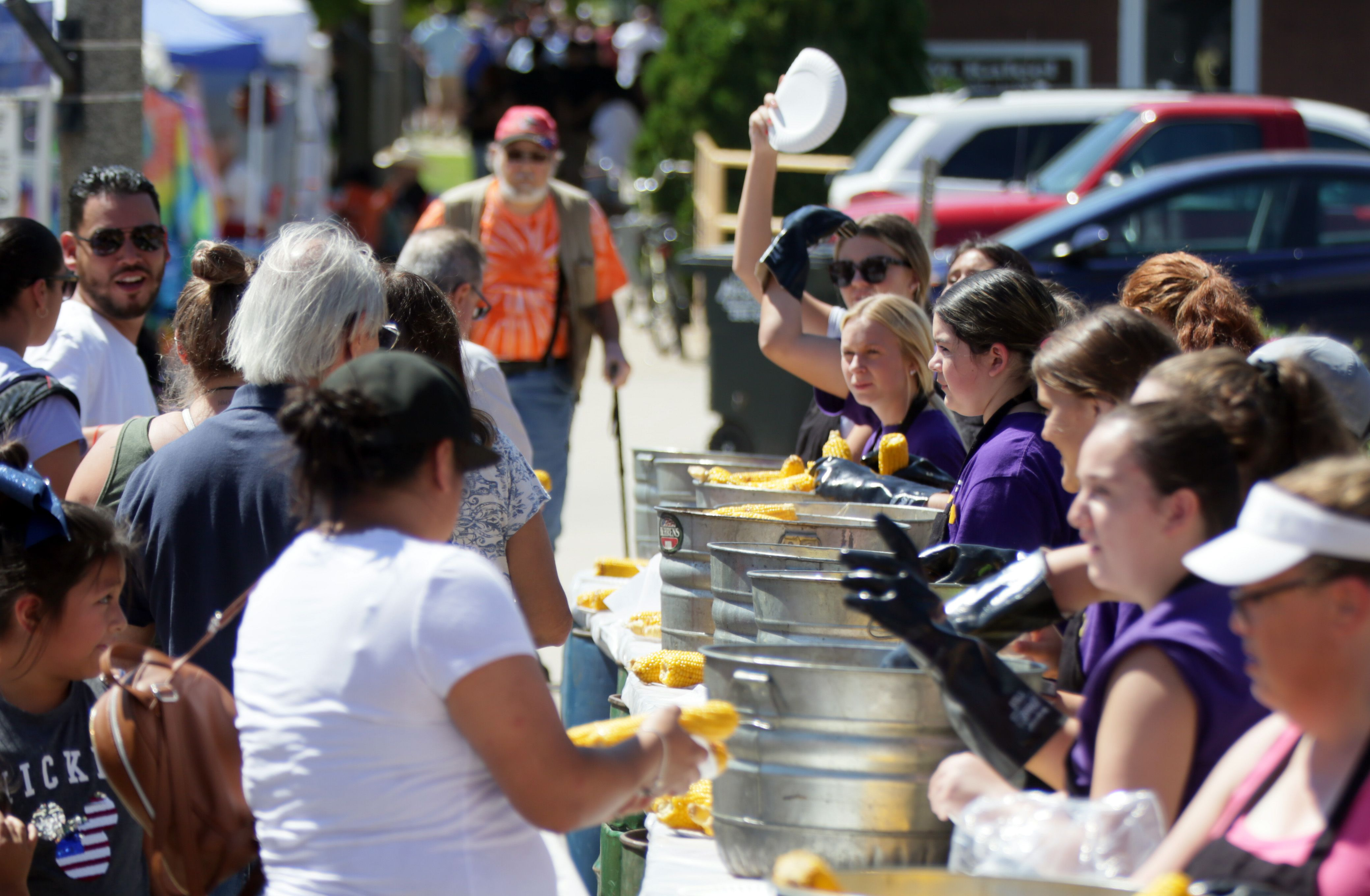 Volunteers hand out free sweet corn during the 74th annual Sweet Corn Festival in Mendota on Sunday, Aug. 15, 2021.