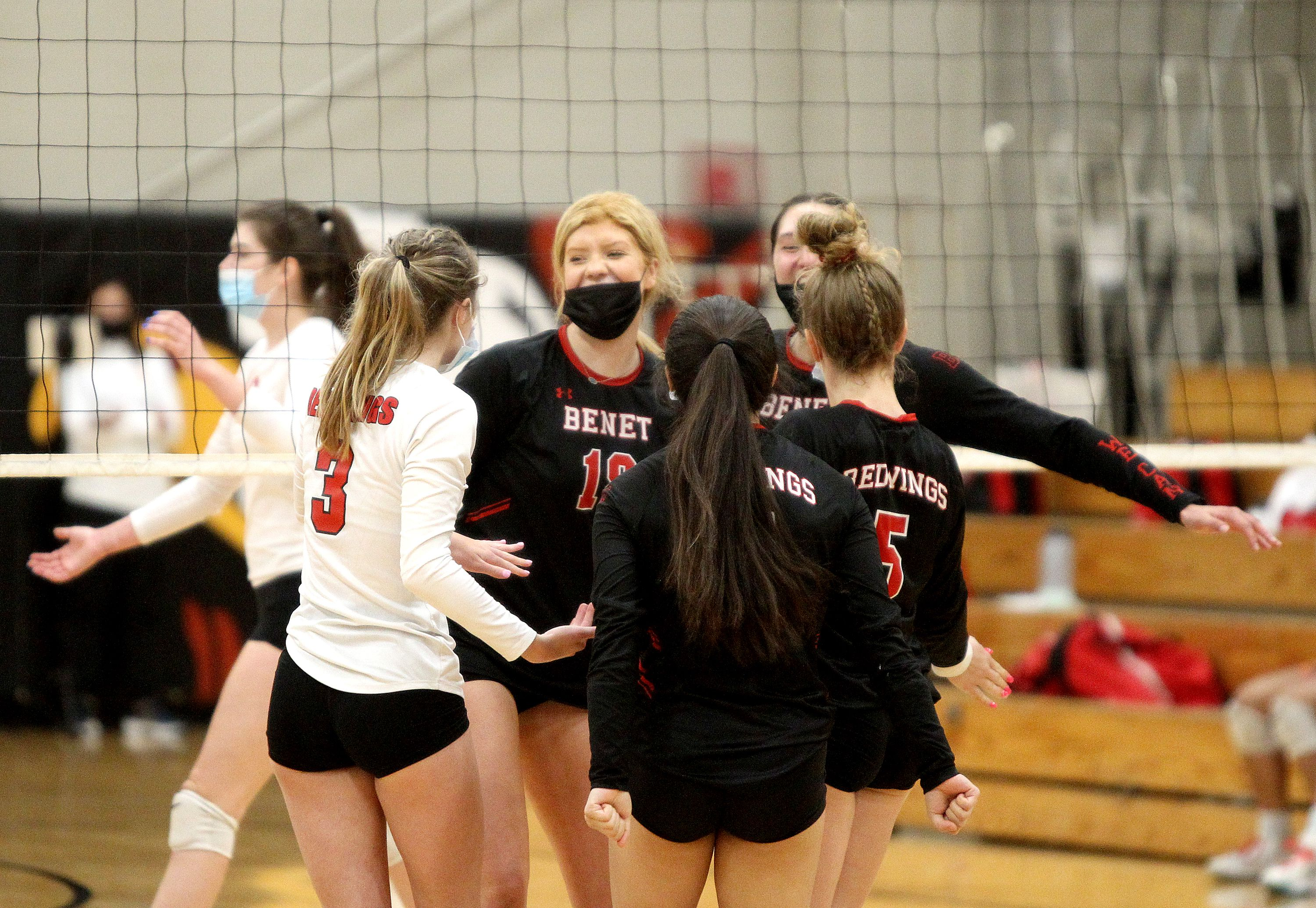 Benet's Rachel Muisenga (center) celebrates a point with her team during the first set of their three-set win over Mother McAuley on Wednesday, April 7, 2021 in Lisle.