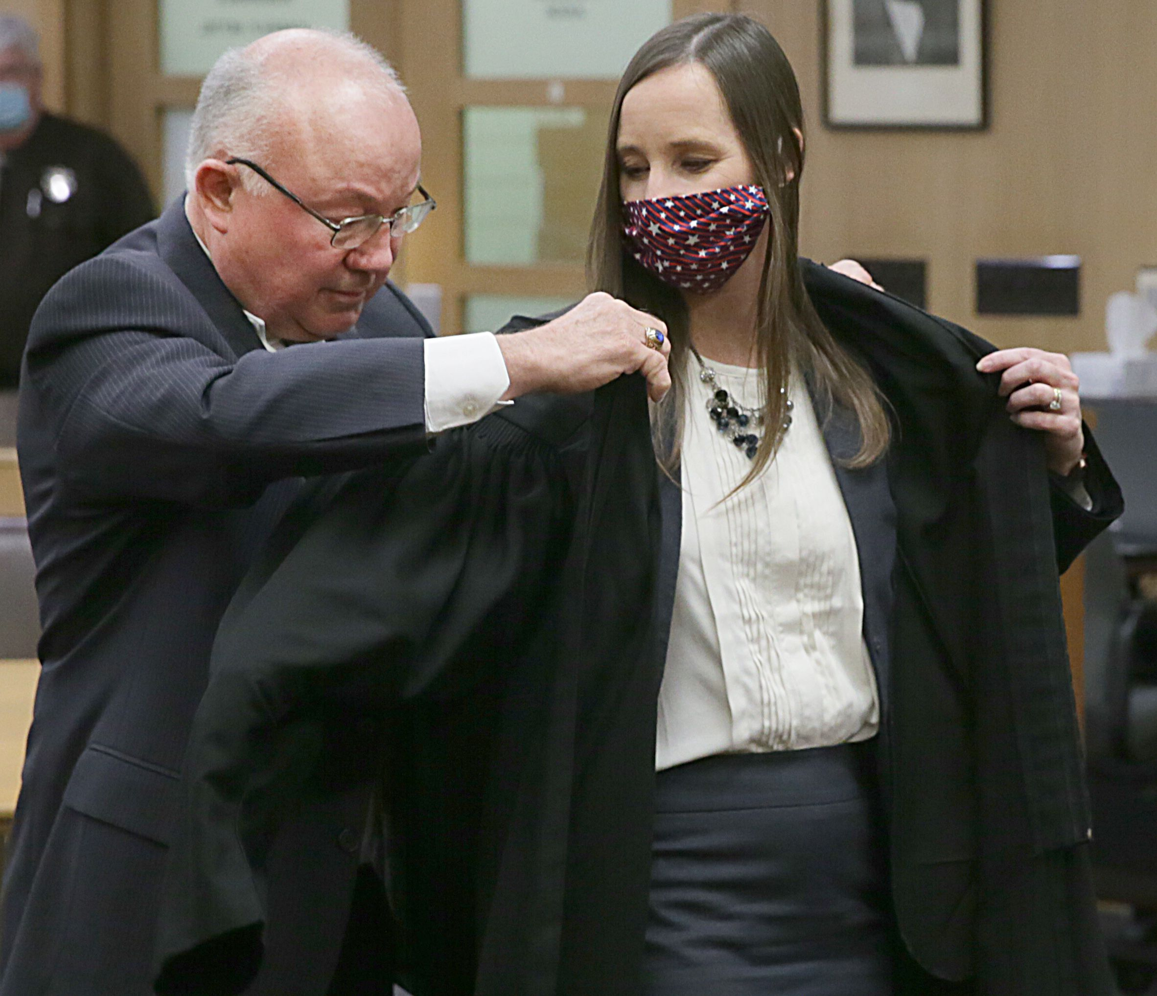 John Cantlin places the judicial robe on his daughter Judge Christina Cantlin-Van Wiggeren shortly after VanWiggeren accepted the oath at the La Salle County Courthouse downtown Ottawa on Monday March 22, 2021.
